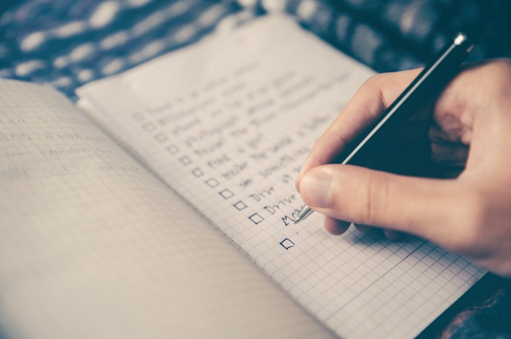 Hand writing a checklist, with list details out of focus
